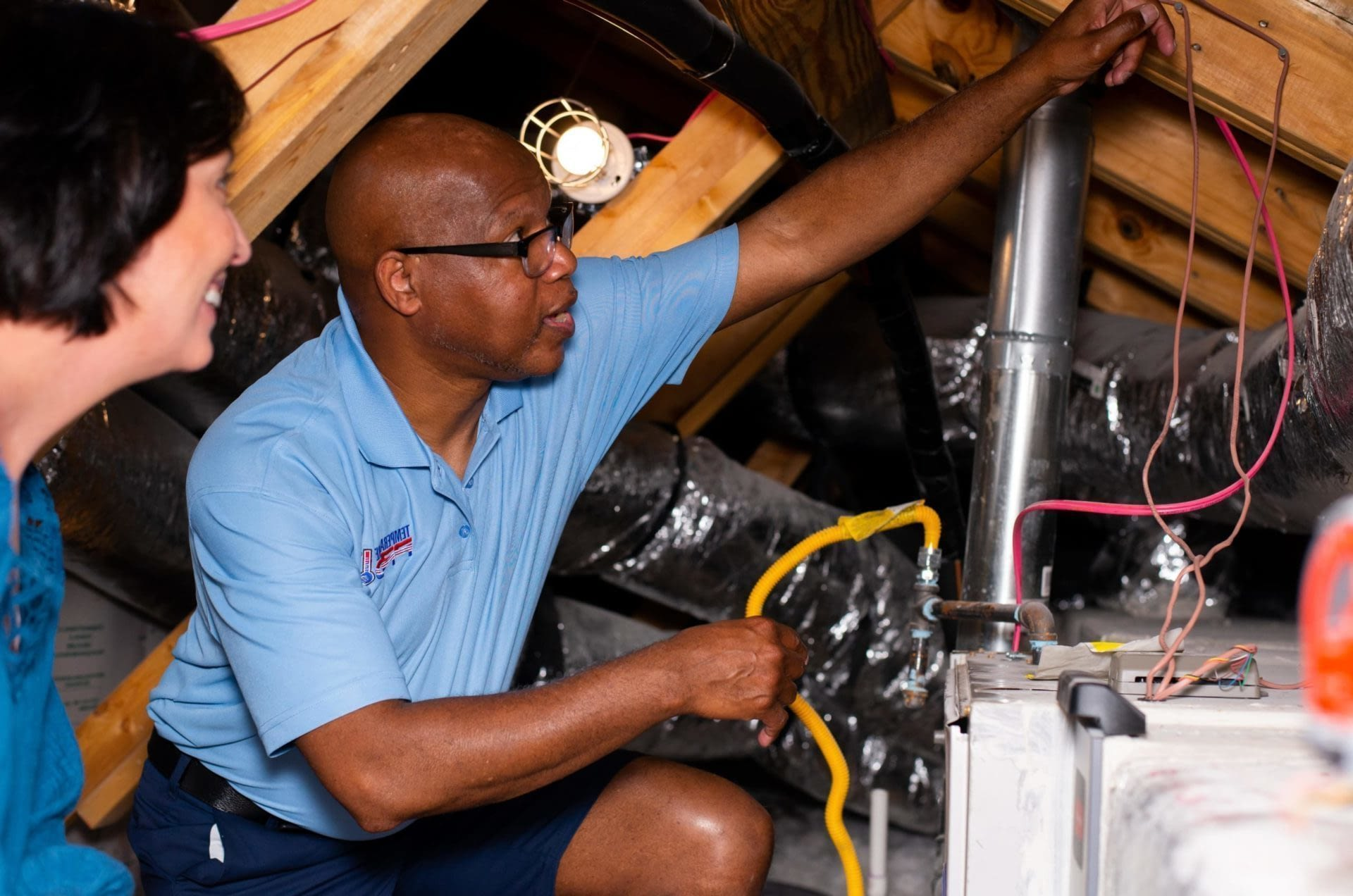 An HVAC technician showing a customer vents and pipes in an attic