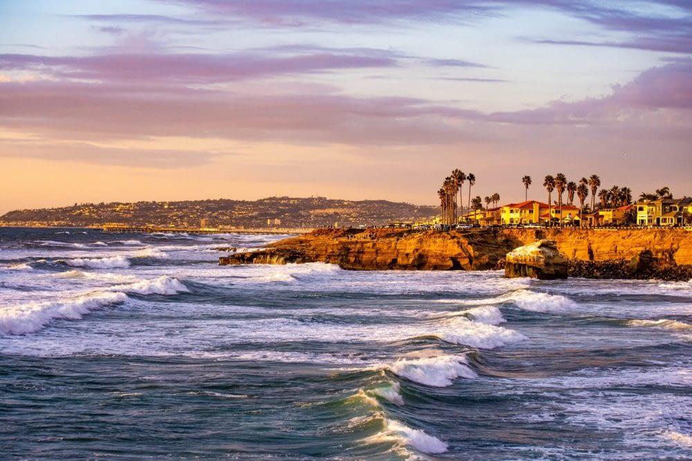 Waves splashing against the San Diego coastline at sunset