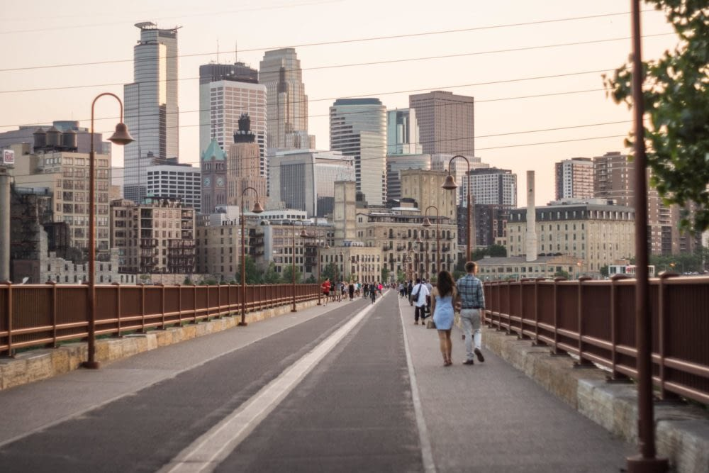 a view of downtown Minneapolis from a bridge with people walking across it