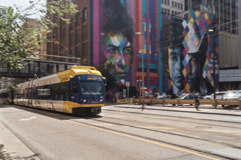 A colorful mural of Bob Dylan with a yellow T metro train in motion