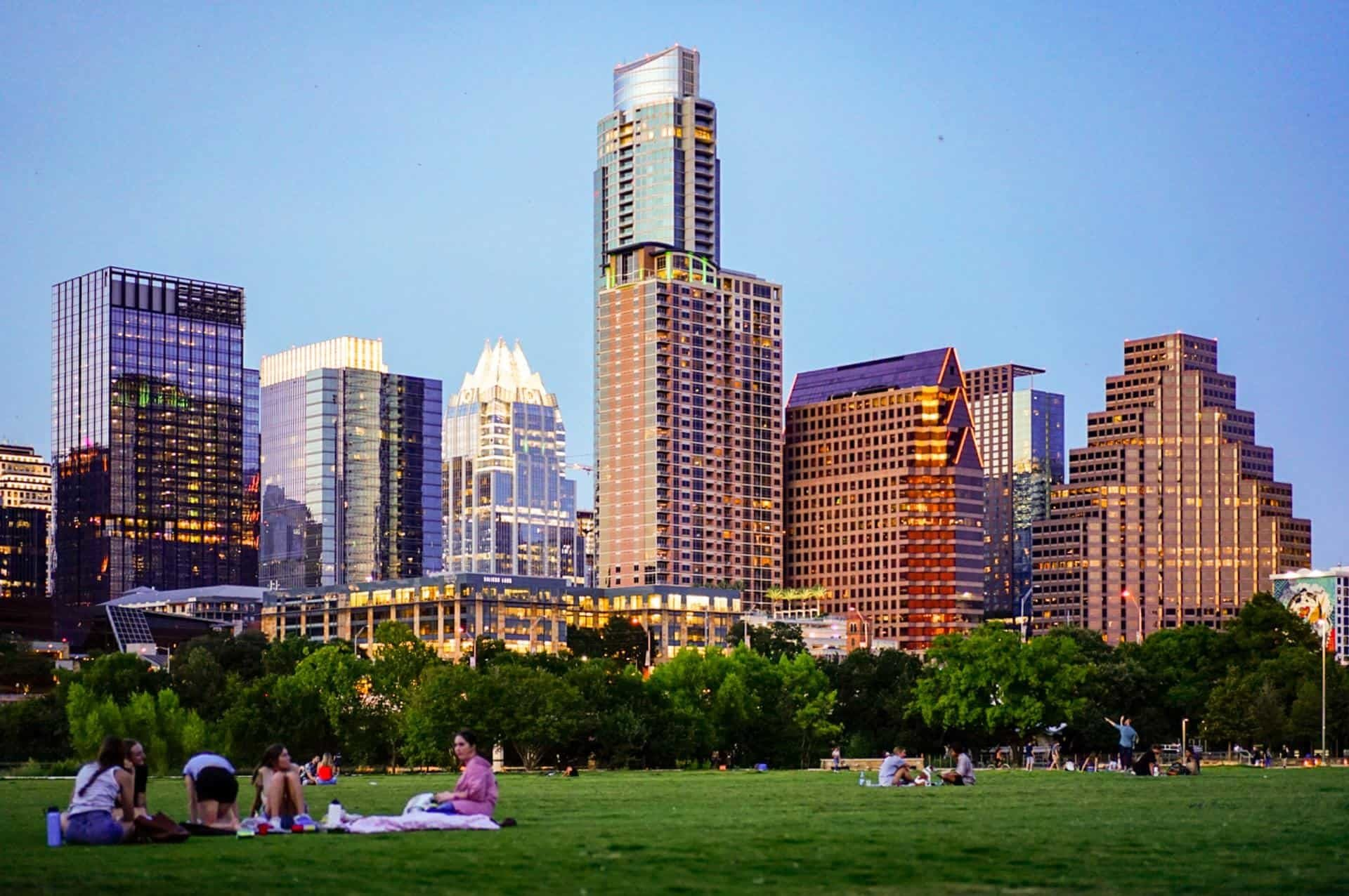 small groups of people sitting in the grass in front of the downtown Austin skyline