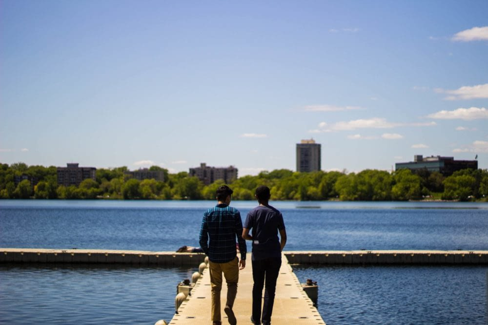 Two people walking on a pier on a lake with some trees and buildings in the background