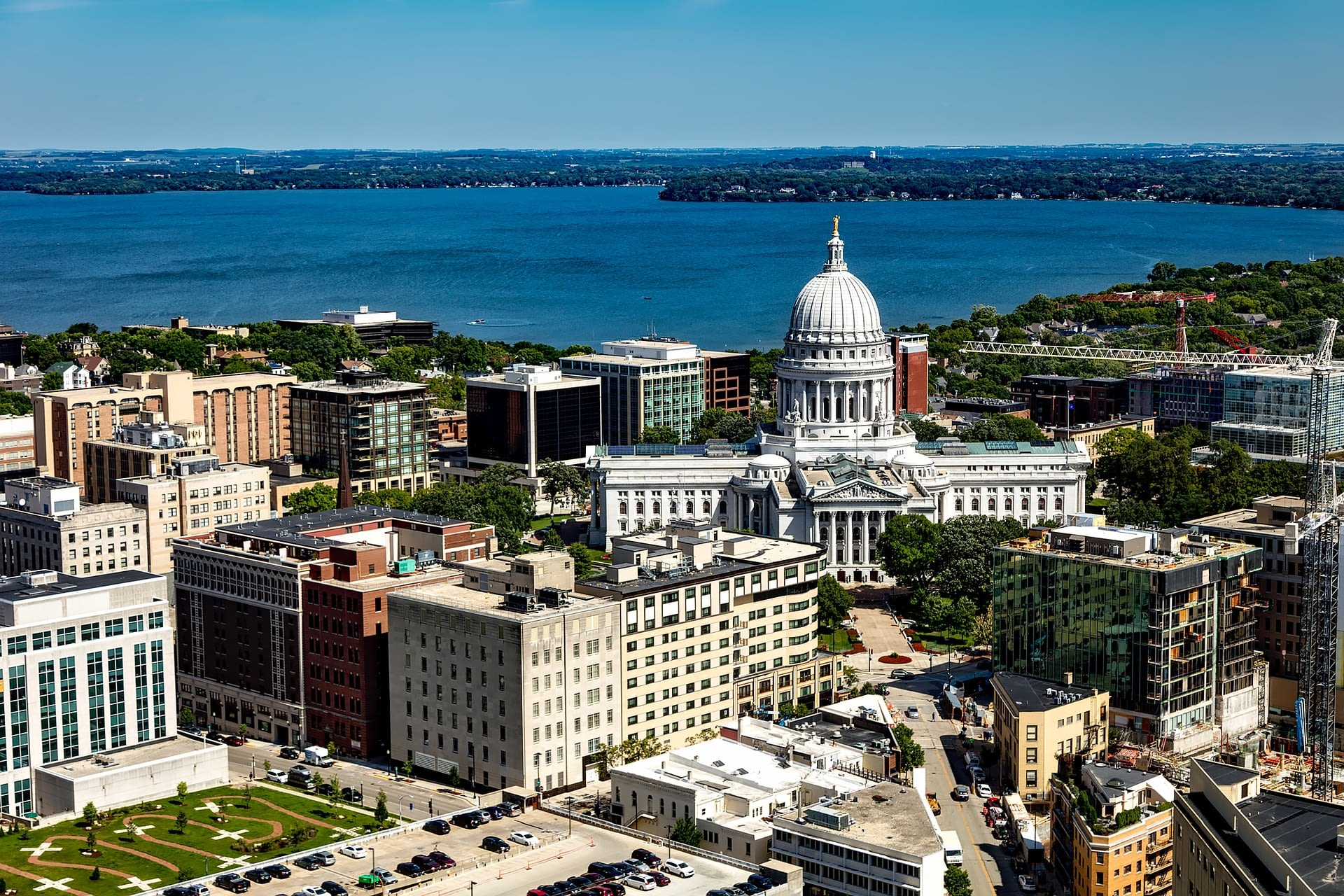 Downtown Madison with the capitol building in the foreground and the lake in background
