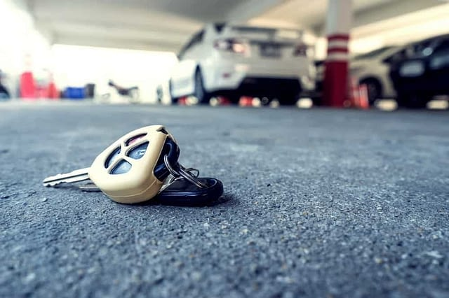 a pair of car keys left on the ground with a car in the background