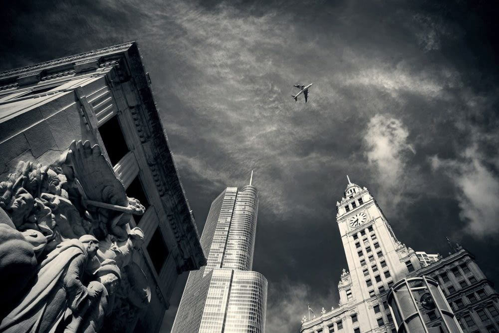 Black and white of Chicago's skyline with a plane flying overhead