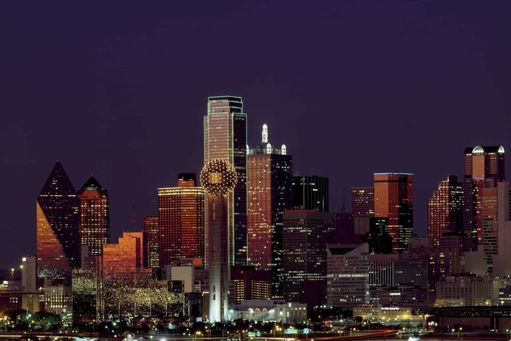 Downtown Dallas skyline with Reunion Tower in the center surrounded by a dark purple night sky