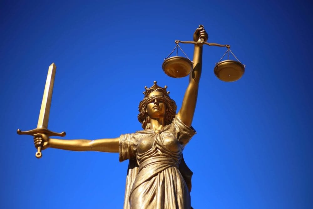 statue of Lady Justice holding scales in one hand and a sword in the other