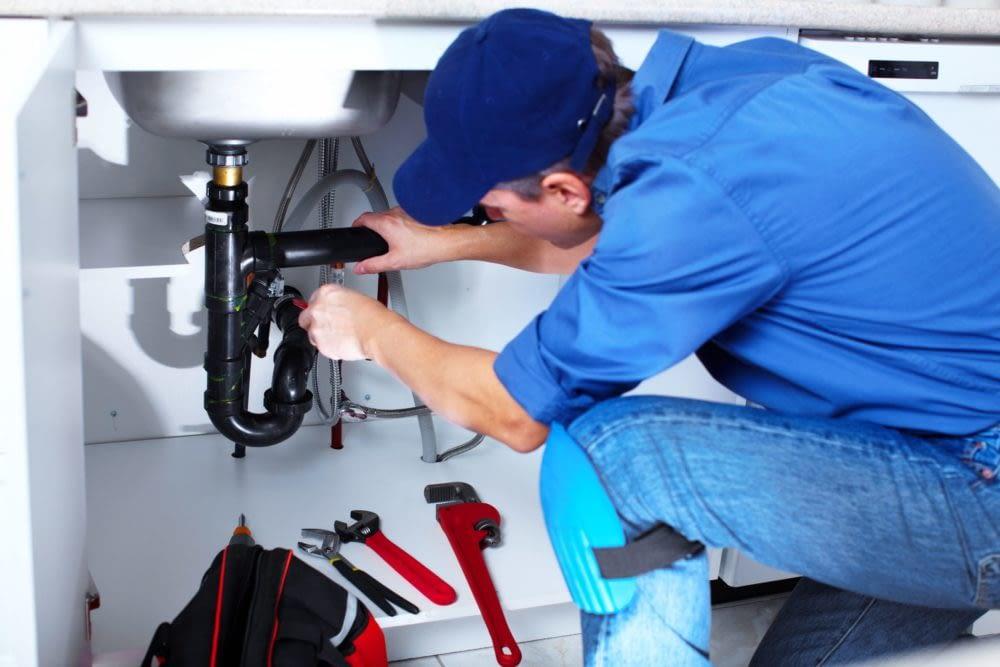 a plumber fixing a pip under a sink