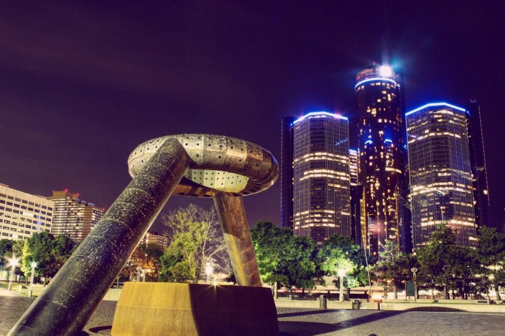 Downtown Detroit at night with a sculpture in the foreground